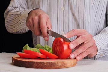 Close up on male hands cutting tomato, making salad. Chief cutting vegetables. Healthy lifestyle, diet food