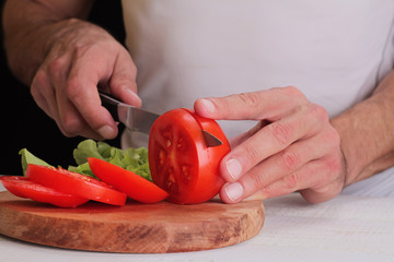 Close up on male hands cutting tomato, making salaCooking at home. Healthy lifestyle, diet food