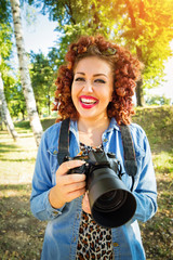 Young female photographer holding digital camera