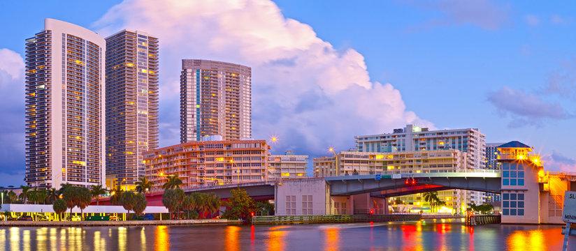 Hallandale Beach Florida, modern buildings and colorful illuminated bridge at sunset