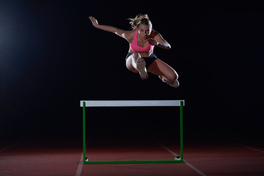 woman athlete jumping over a hurdles