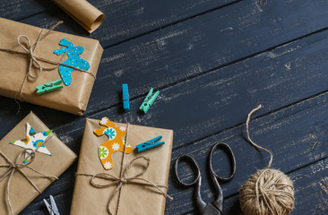Christmas gifts in kraft paper on a dark wooden surface. vintage and rustic style