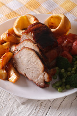 pork with potatoes, fresh vegetables and Yorkshire pudding, vertical