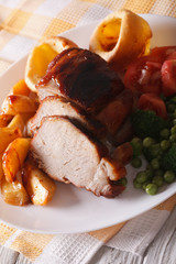 Sunday roast: pork with vegetables and Yorkshire pudding. Vertical