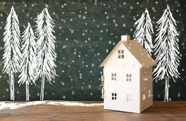 photo of toy house in front of chalkboard with winter concept drawings