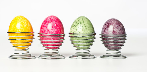 Multicolor hand painted easter eggs in metal holders on white background