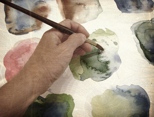 aged and worn vintage photo of artist hand working on artwork