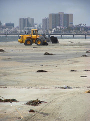 tractor moving sand on beach with city buildings in background