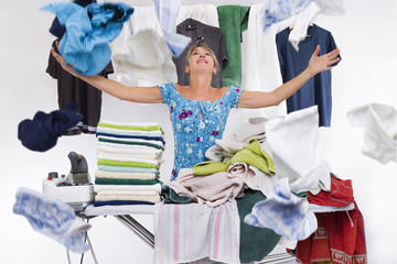 woman behind an ironing board packed with towels iron launches top clothes just ironed