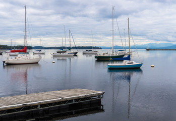 sail boats moored in lake  with breakwater and lighthouse seen before the Adirondack mountains in the distance