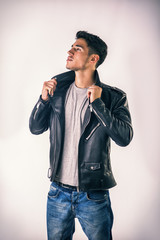 Handsome young man wearing leather jacket, t-shirt and jeans