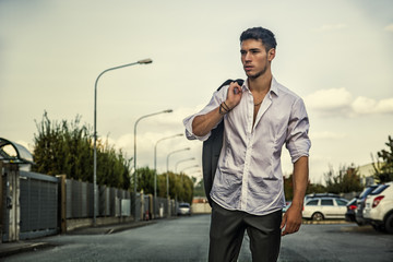 Handsome young man in elegant white shirt standing outdoor