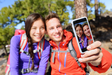 Selfie couple using smart phone camera hiking