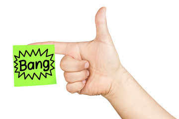 Hand in a gesture to mimic handgun with green postit glued on forefinger with bang text isolated