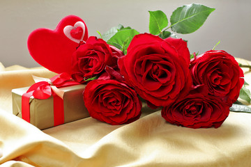 Bouquet  of red roses  with hearts,  on golden tablecloth