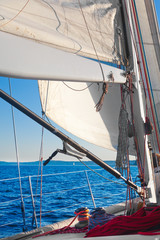 Sailing, with closeup of sail, rigging and ropes. Afternoon warm light.