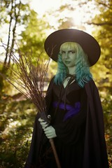 Young girl with green hair and broom in suit of witch in forest. Halloween time