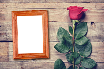 Vintage rose and blank photo frame on old wooden background