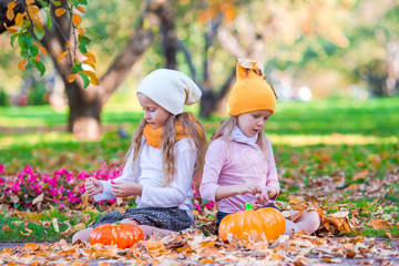Wall Mural - Adorable little girls with pumpkins outdoors at beautiful autumn
