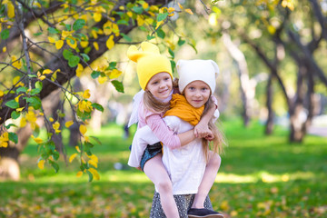 Wall Mural - Adorable little girls have fun outdoors at beautiful autumn day