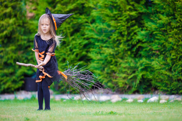 Little adorable girl in halloween costume having fun on