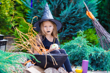 Wall Mural - Adorable girl wearing witch costume on Halloween at autumn day