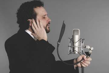 artist of the song, singer suit and microphone
