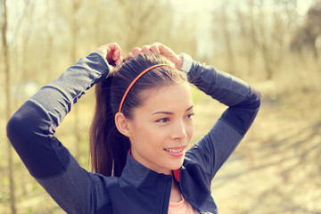 Woman tying hair in ponytail getting ready for run