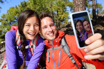 Happy friends hikers taking selfie on hiking trip