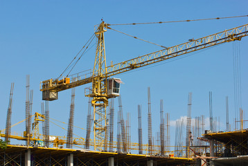 Construction site with crane isolated on blue sky.