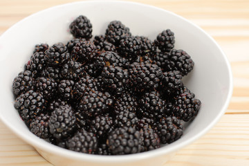 Blackberries  in a white bowl on wooden table