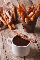 Spanish cuisine: churos and hot chocolate on the table. Vertical