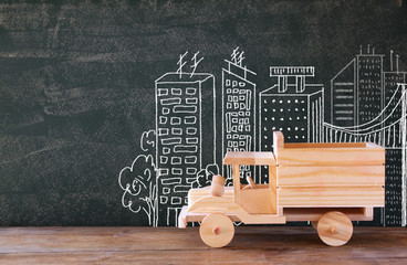 photo of wooden toy truck in front of chaklboard with city illustration.