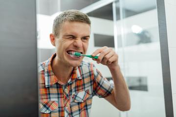 man cleans his teeth in the bathroom