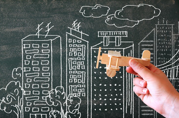 close up photo of woman's hand holding wooden toy airplane against chalkboard with city illustration.success and inspiration concept