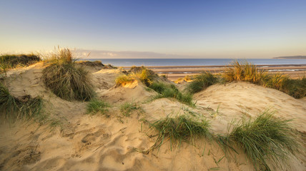 Beautiful sunrise over sand dunes system on yellow sand golden b