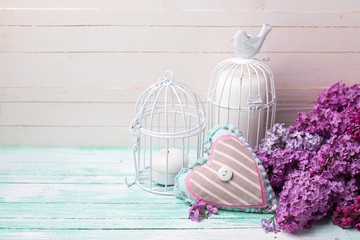 Background  with fresh lilac flowers, candles in decorative bird