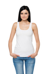 A brunette woman in a white tank top and denims. Hands are in the pockets. Isolated.