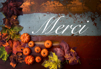 french word 'merci' (thank you) on wood