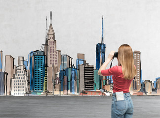 Young beautiful lady in casual clothes is taking a pictures of the drawn New York. A concept of modern tourism.
