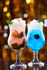 Glasses of cocktails with ice on blurred lights background