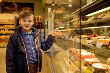 Little boy near display with cakes in a grocery store