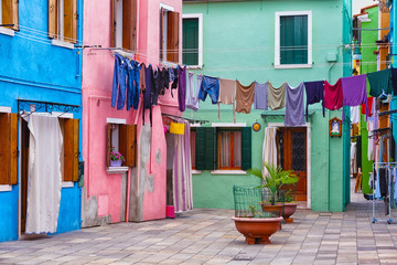 small yard on Burano's island with multi-colored houses and the linen hanged on a rope