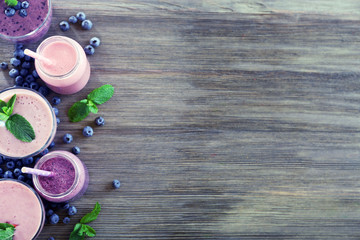 Berry yogurts in a row on wooden background, empty space