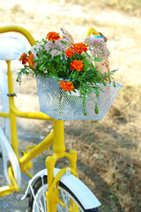 Beautiful yellow bicycle with bouquet of flowers, milk bottle and bread in basket, outdoors