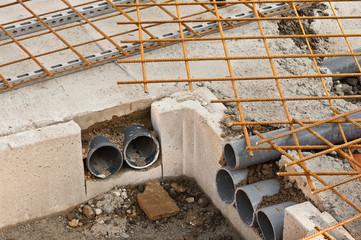 Leerrohr läuft in einen Kabelschacht in einem Betonfundament