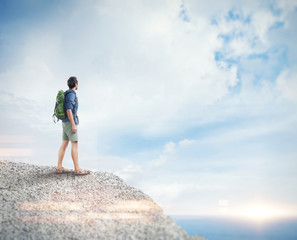 Young man with backpack on the rock. Visual effects