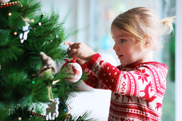 Little girl decorating christmas tree with toys and baubles. Cute kid preparing home for xmas celebration.