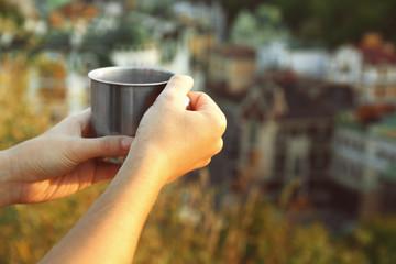 Metal touristic tea cup in female hands