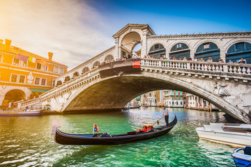 Gondola with Rialto Bridge at sunset, Venice, Italy
